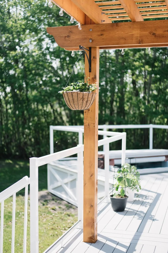 Hanging baskets and potted veggies on a grey deck with cedar pergola