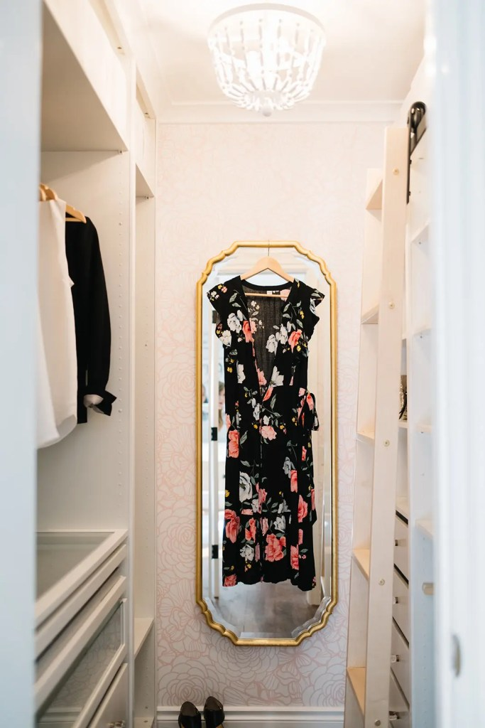 A long mirror with a dress hanging ready to wear