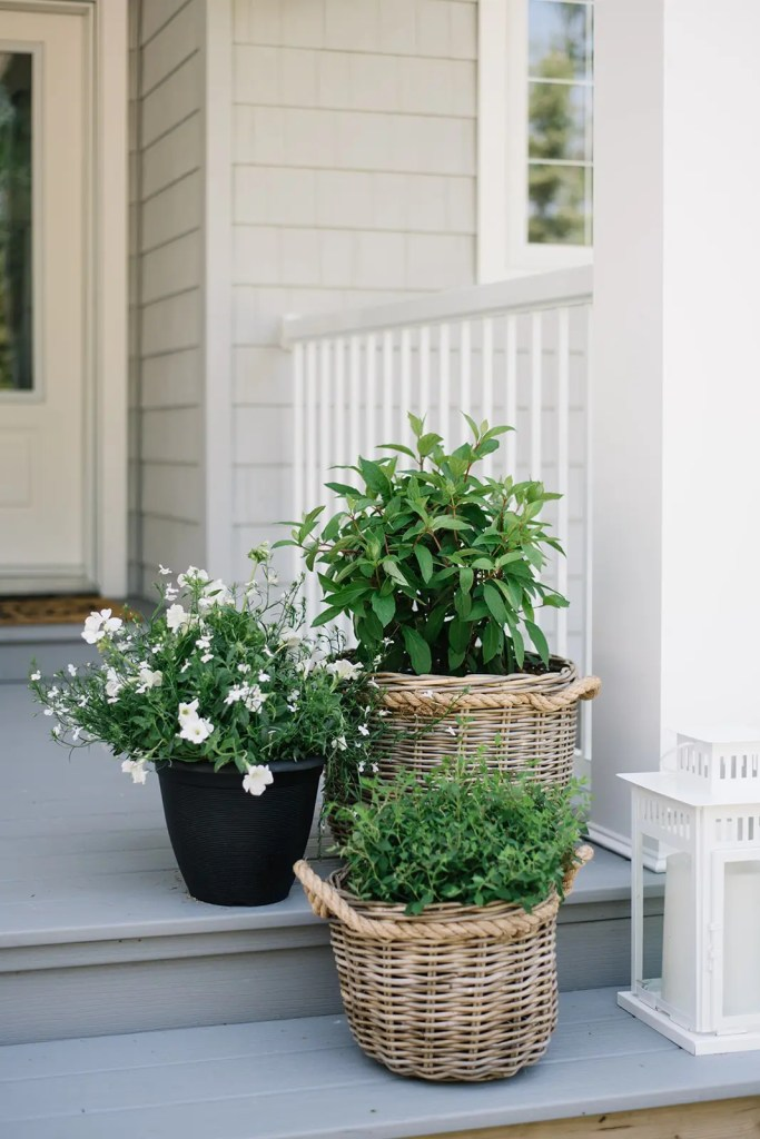 Woven baskets act as cache pots on the front porch.