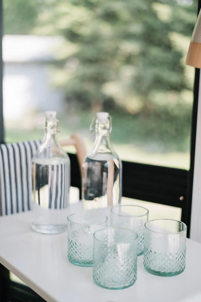 Pretty aqua water glasses are a summery touch in this outdoor dining space