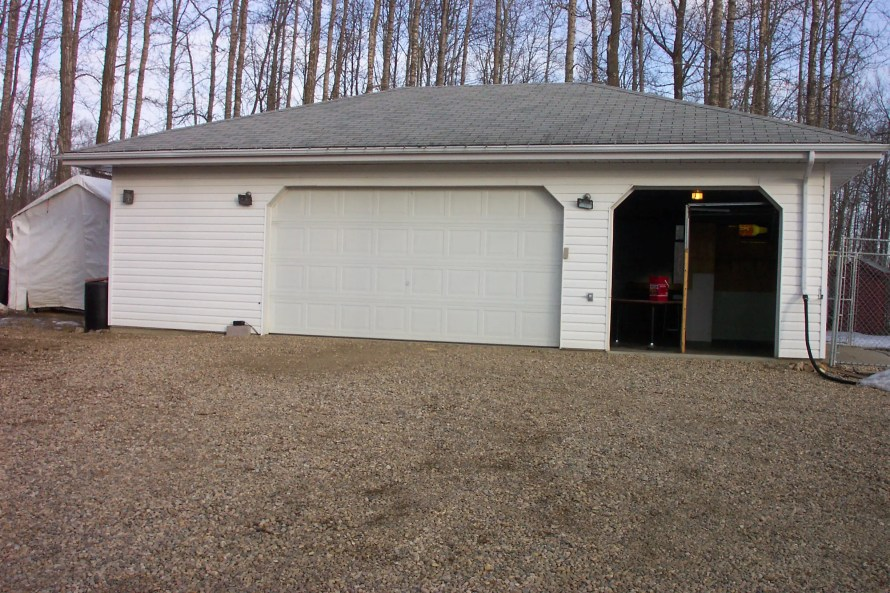 A garage before renovation with white siding and garage doors.