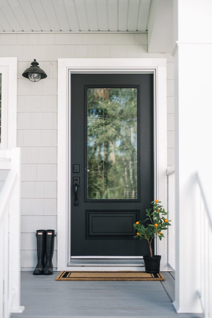 Classic black exterior door with 3/4 glass and little orange tree, mat and rubber boots sitting on the porch.