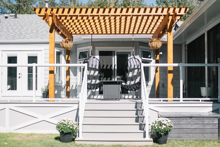 Cedar pergola with swings on the back deck of modern country farmhouse.