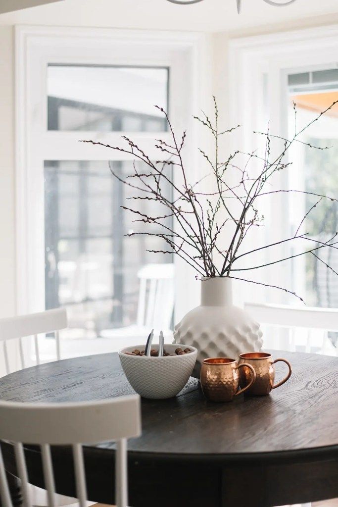 branches in a vase and fresh nuts make a pretty fall vignette