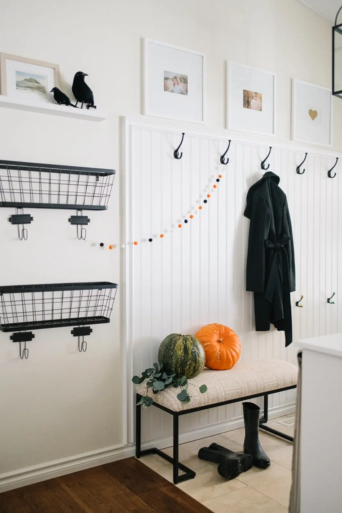 Subtle Halloween entryway with pumpkins and pom pom garland