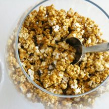 overhead of caramel corn in clear glass bowl with metal scoop