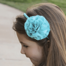 side profile of girl wearing aqua frayed flower headband