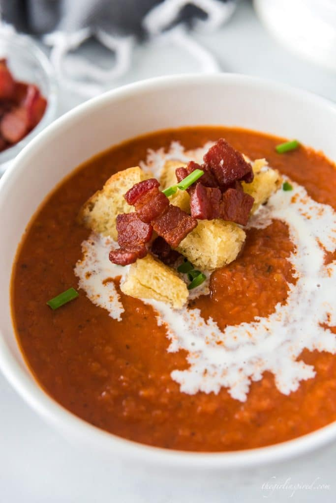 tomato bisque in white bowl with bacon, croutons, chives and drizzle of cream on top