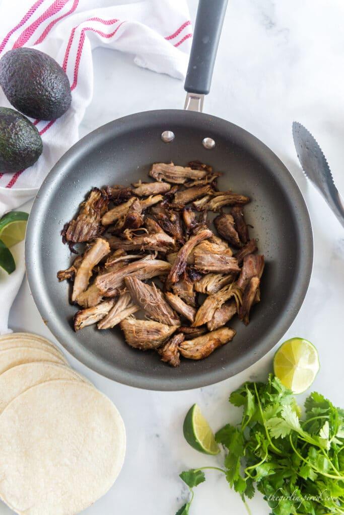browned carnitas in frying pan, avocados, tortillas, cilantro, and lime