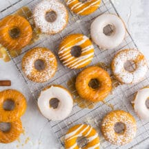 overhead of two ingredient pumpkin donuts on cookie sheet with cinnamon sticks and a variety of toppings - powdered sugar, white frosting, caramel drizzle