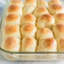 clear glass baking dish with dinner rolls and white and blue floral linen