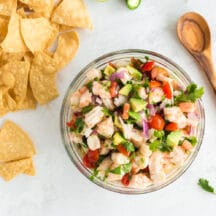 overhead shot of shrimp ceviche in glass bowl with wooden spoon and tortilla chips laying to the side