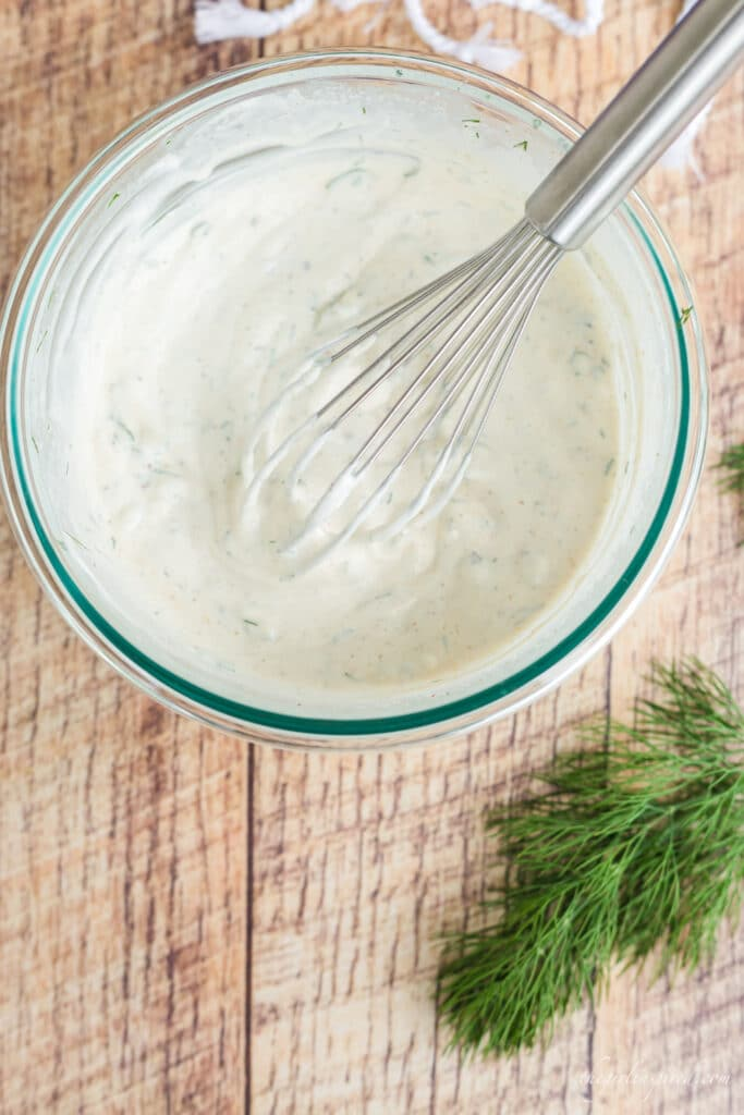glass bowl of dill dip with wire whisk and sprig of fresh dill