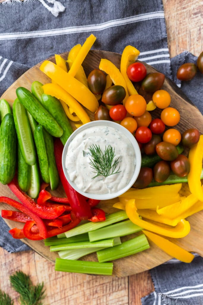 white bowl of dill dip with tomatoes, colored bell peppers, and celery on wooden cutting board with grey linen