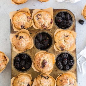overhead view of blackberry muffins in muffin tin with some of the muffin spots filled with blackberries and a white linen
