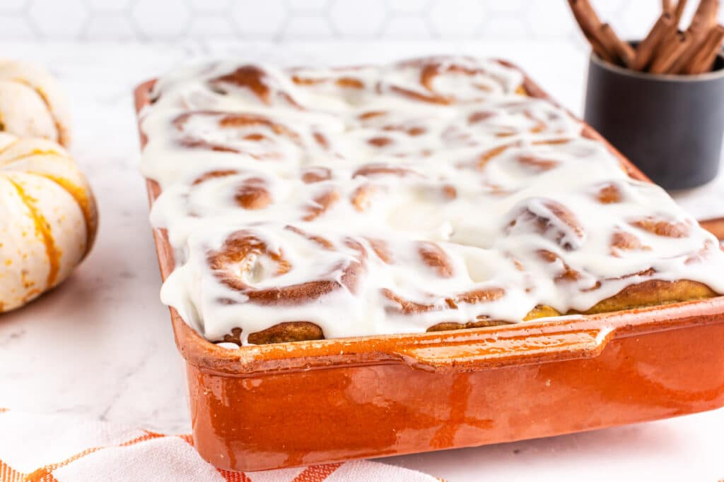 side view of orange baking dish with baked and frosted pumpkin cinnamon rolls
