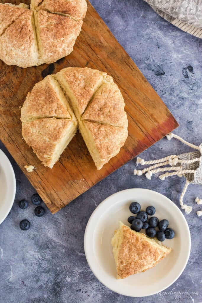 Scone rounds on wooden board with one scone triangle removed onto plate with blueberries