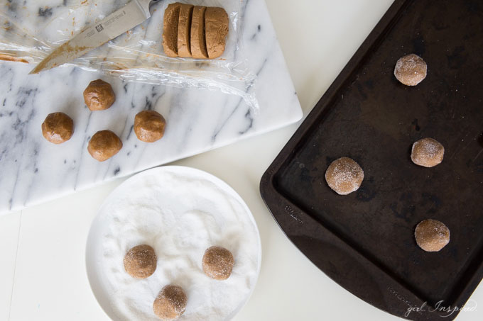 balls of ginger cookie dough on marble slab, in dish rolled in sugar and placed on cookie sheet.