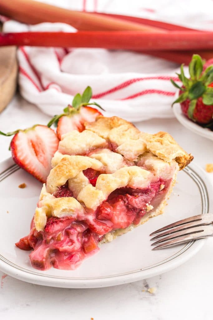 slice of strawberry rhubarb pie on plate with halved fresh strawberries and red/white linen in background