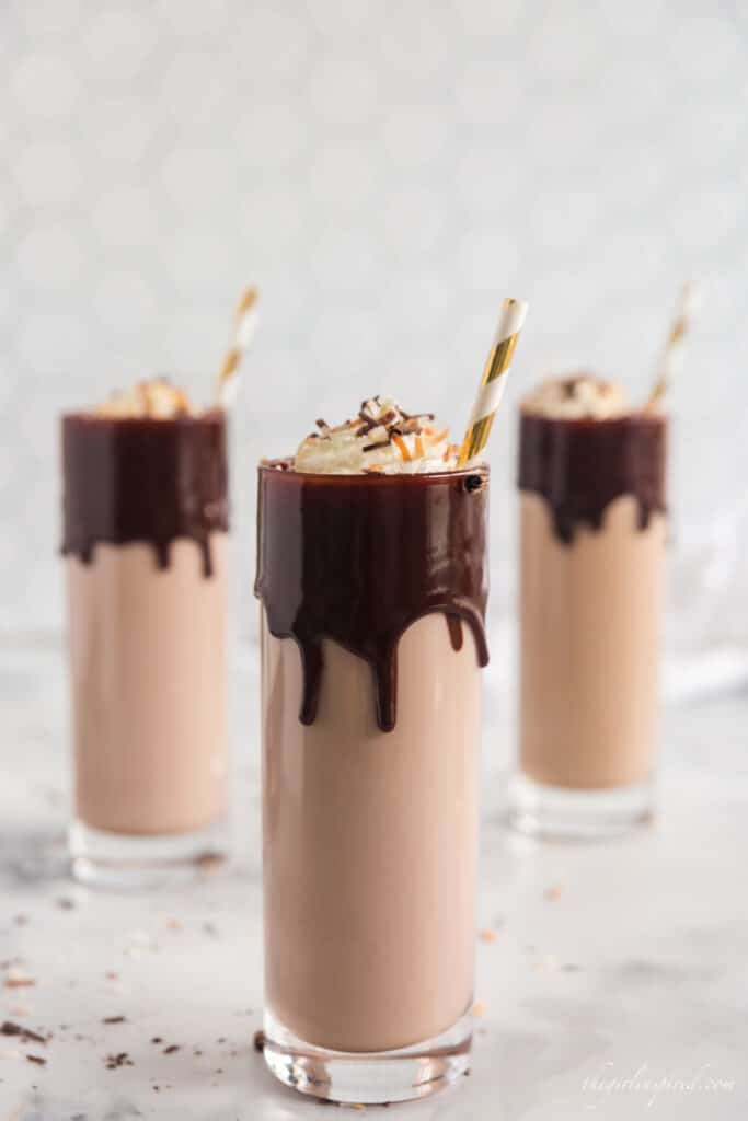 three tall glasses of coconut rum cocktail with chocolate dripping from rim, filled with chocolate milk and liquor and topped with whipped cream and gold stripes straws