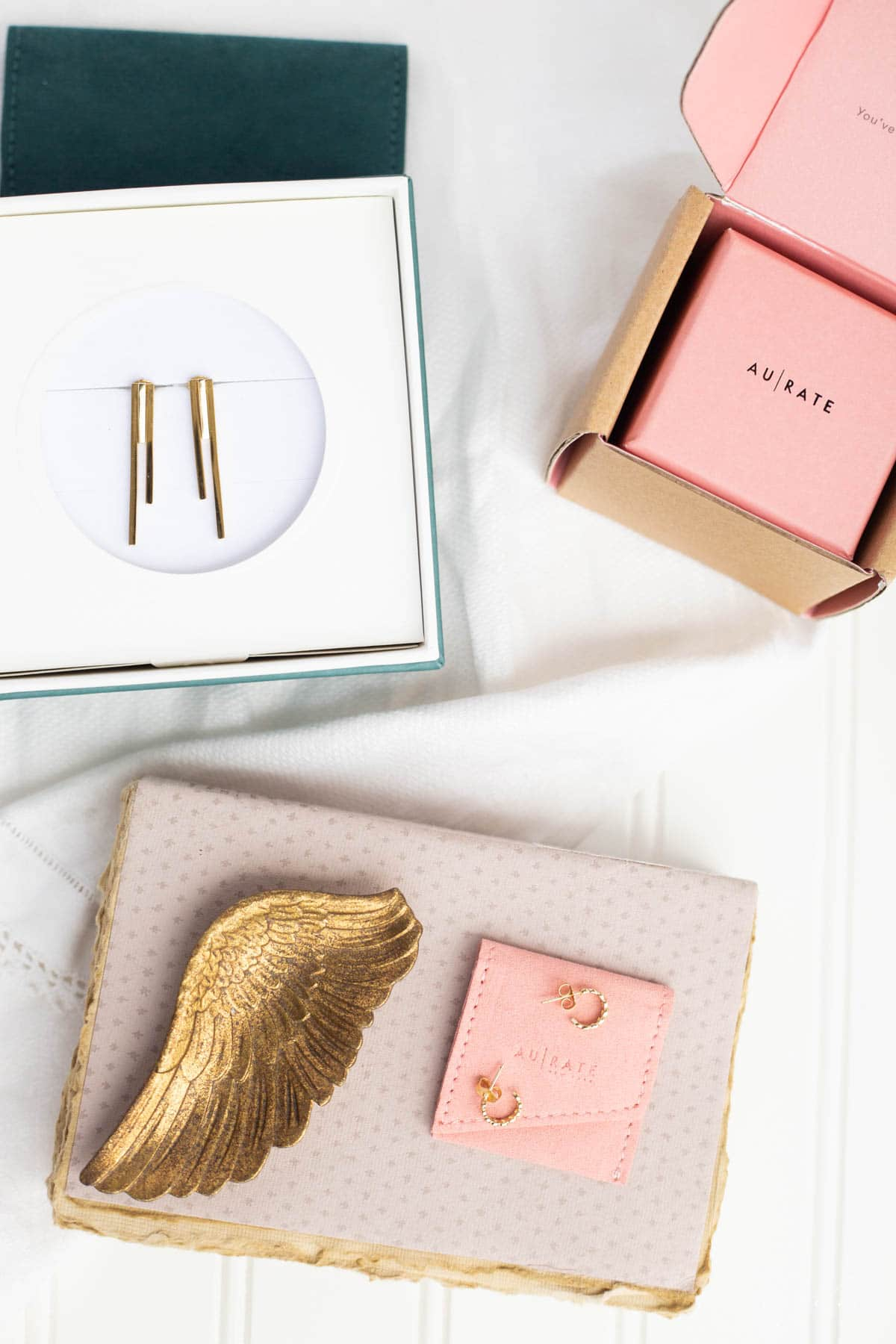 small pink jewelry box, gold bar earrings in a teal jewelry box, small heart gold hoop earrings on a pink suede case with gold angel wing jewelry dish set on a vintage grey book.