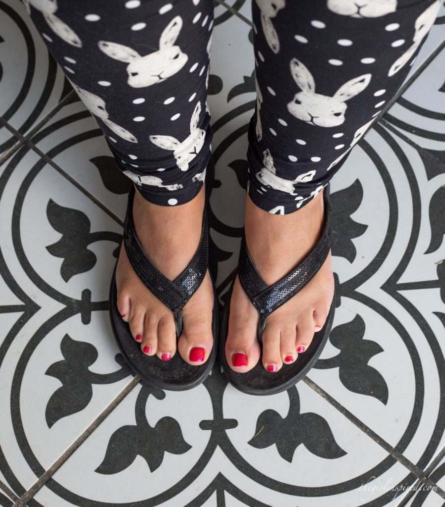 feet in black flip flops on a black and white tile floor with black and white bunny patterned leggings