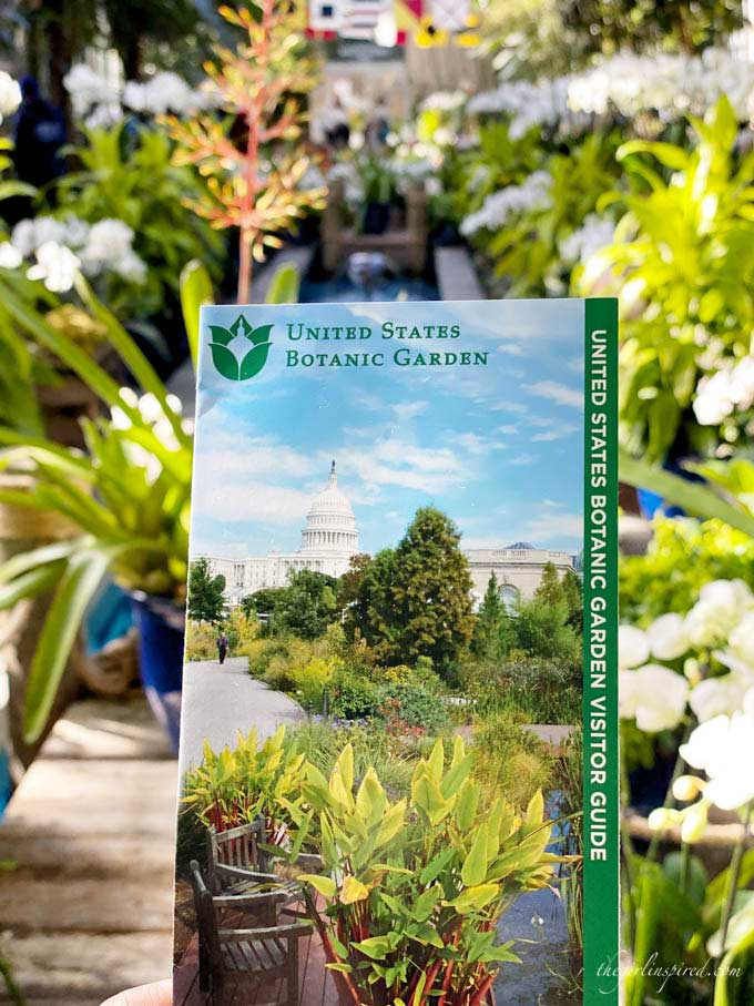 National Botanic Garden brochure with white, green, and orange flowers in the background.