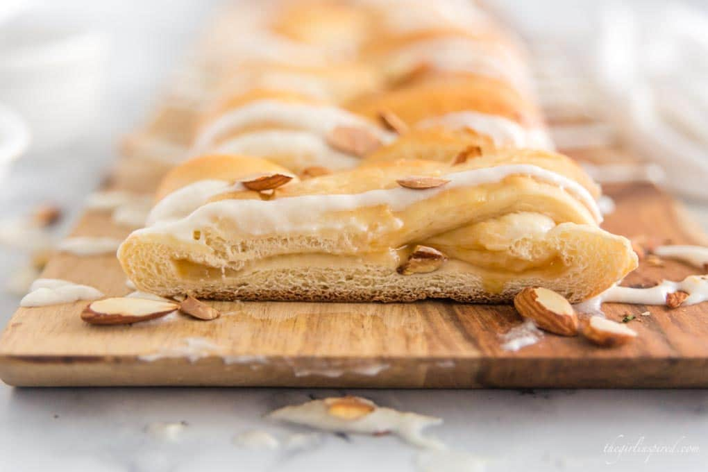 braided sweet bread on cutting board with almonds and icing
