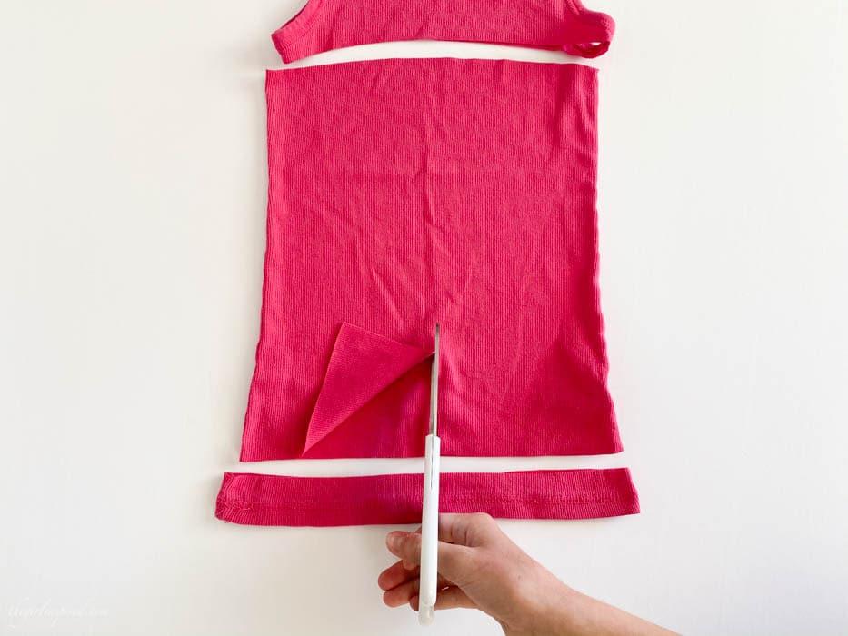 white scissors cutting pink tank top fabric