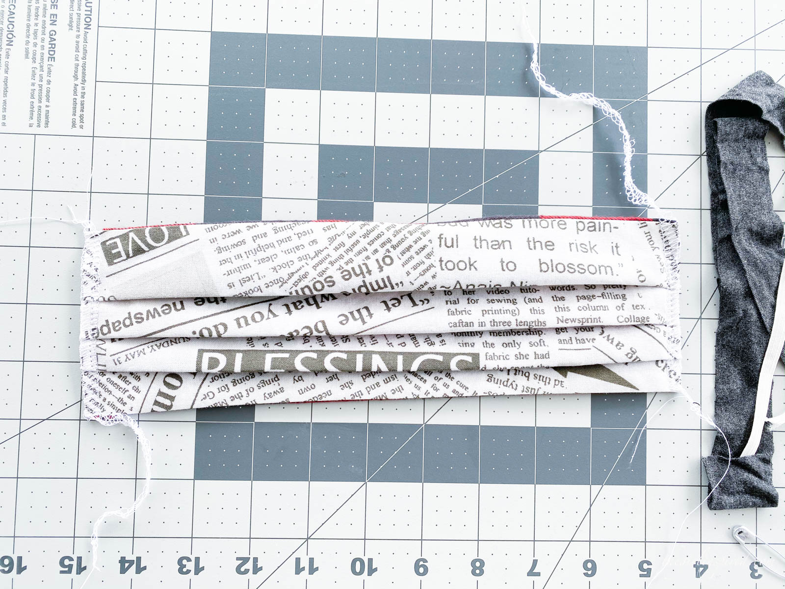 serged newsprint mask on rulered mat