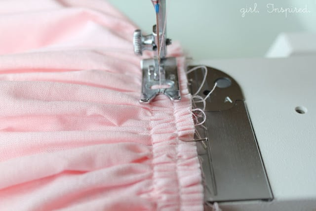 close up of sewing machine foot sewing over pink fabric gathers