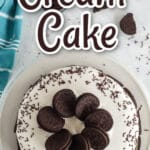overhead photo of oreos and chocolate sprinkles on ice cream cake on white plate with aqua linen