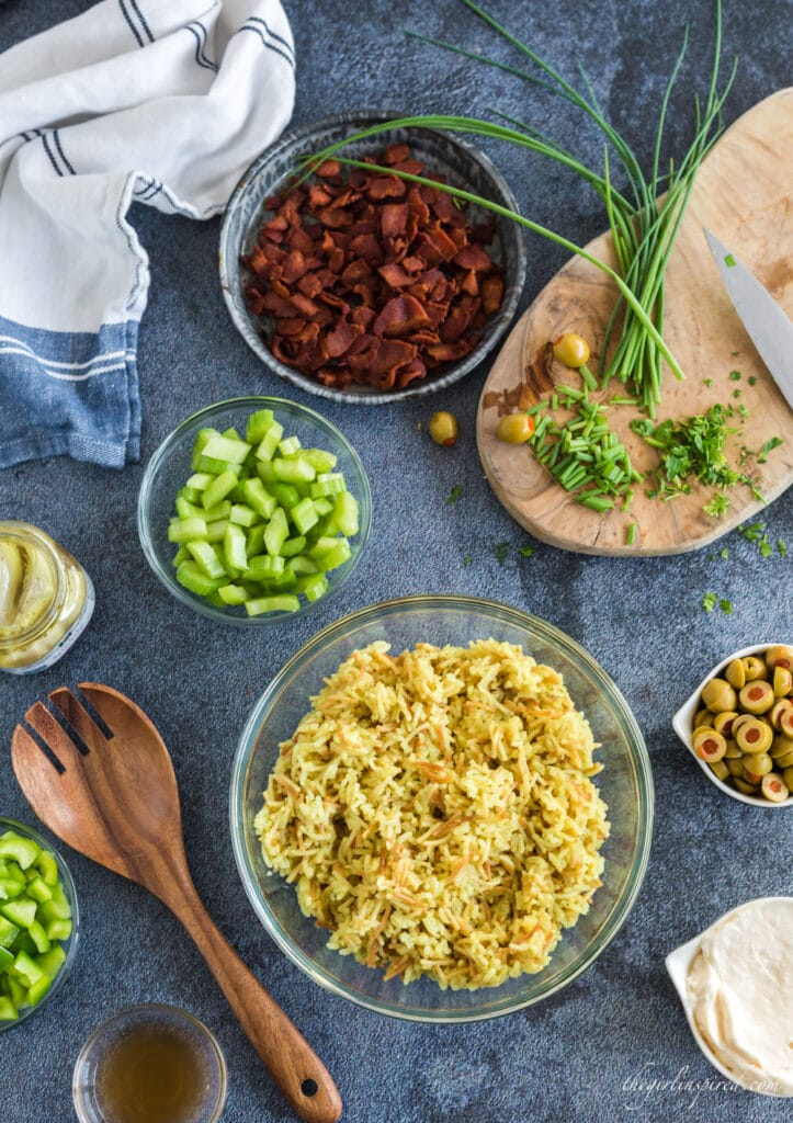 Rice a Roni, bacon, chopped celery, green olives, mayonnaise in separate glass bowls, chives on cutting board, wooden serving spoon