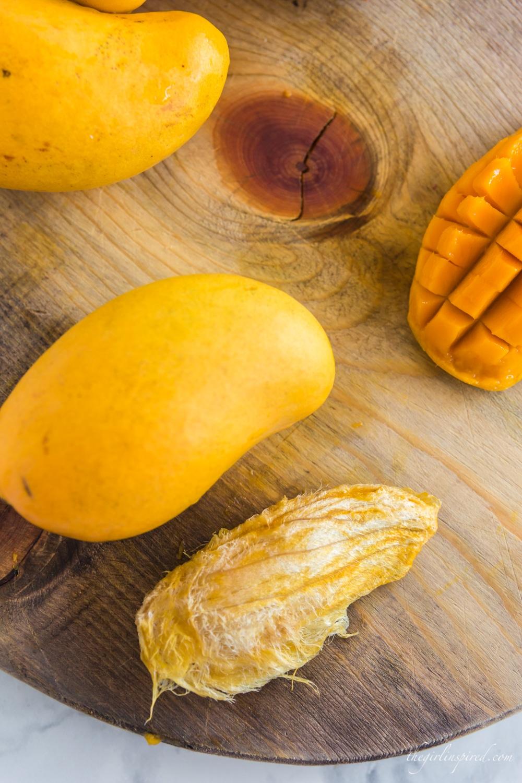 mango pit lying next to whole mango on a wooden cutting board