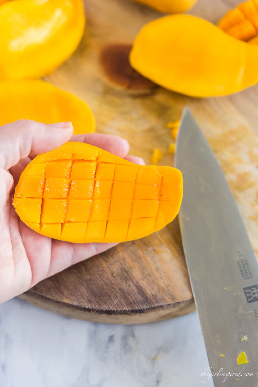 knife, wooden cutting board, and cube pattern cut into mango flesh