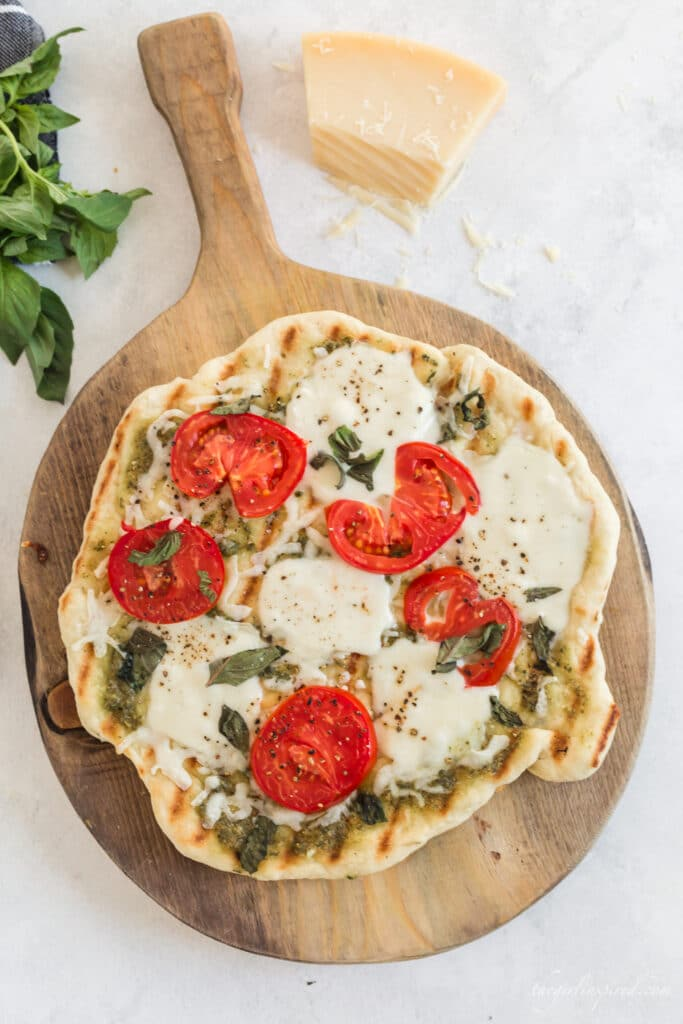 grilled pizza with tomatoes, basil, and melted cheese on wooden board with parmesan, basil leaves, and grey linen in background