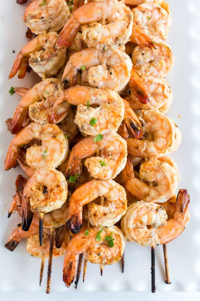 grilled shrimp skewers stacked on white plate