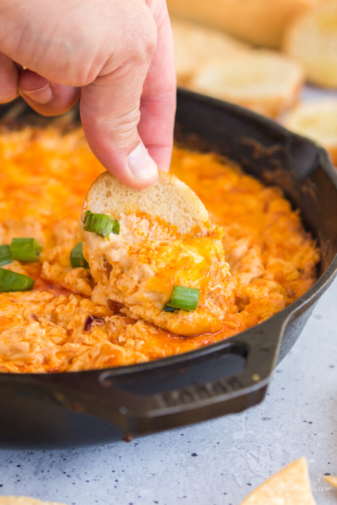 close up photo of chip scooping buffalo chicken dip in cast iron pan