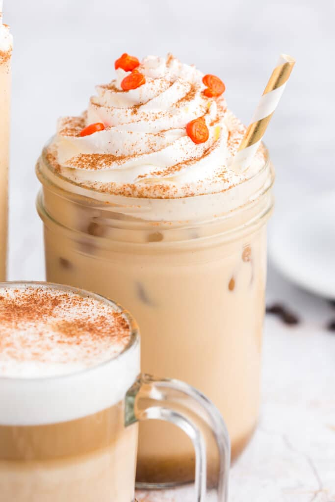 close up of iced pumpkin spice latte in mason jar with gold striped straw, whipped cream swirl, and pumpkin sprinkles