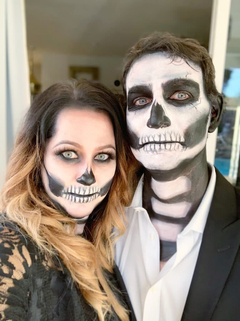 head shot of couple with skeleton face makeup