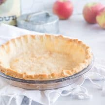 pie crust in glass pie plate on white dishcloth with flour tin and apples in background