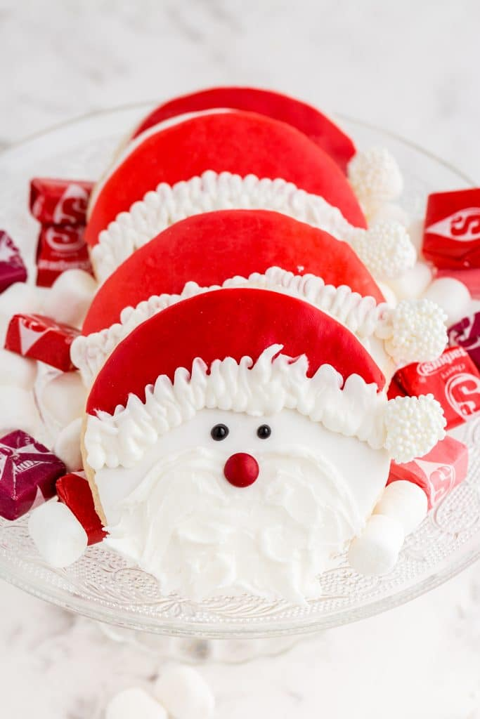 santa claus cookies on glass cake stand with starburst and marshmallows scattered around
