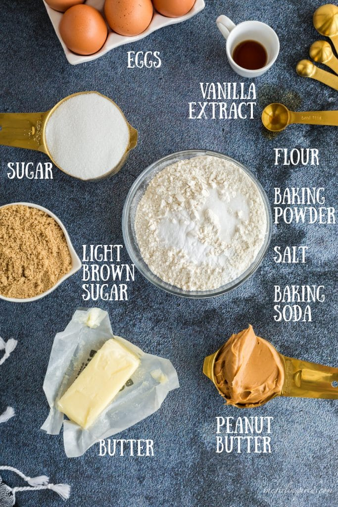 ingredients for peanut butter cookie recipe: flour, salt, baking soda, and baking powder in glass bowl, sugar and peanut butter in gold measuring cups, stick of butter in wrapper, brown eggs, vanilla in white cup, and brown sugar in white cup with text overlay