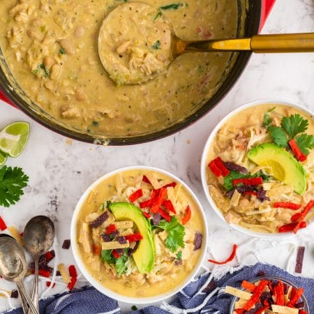 green chili chicken soup in white bowls and red dutch oven, topped with avocado slices and colorful tortilla strips