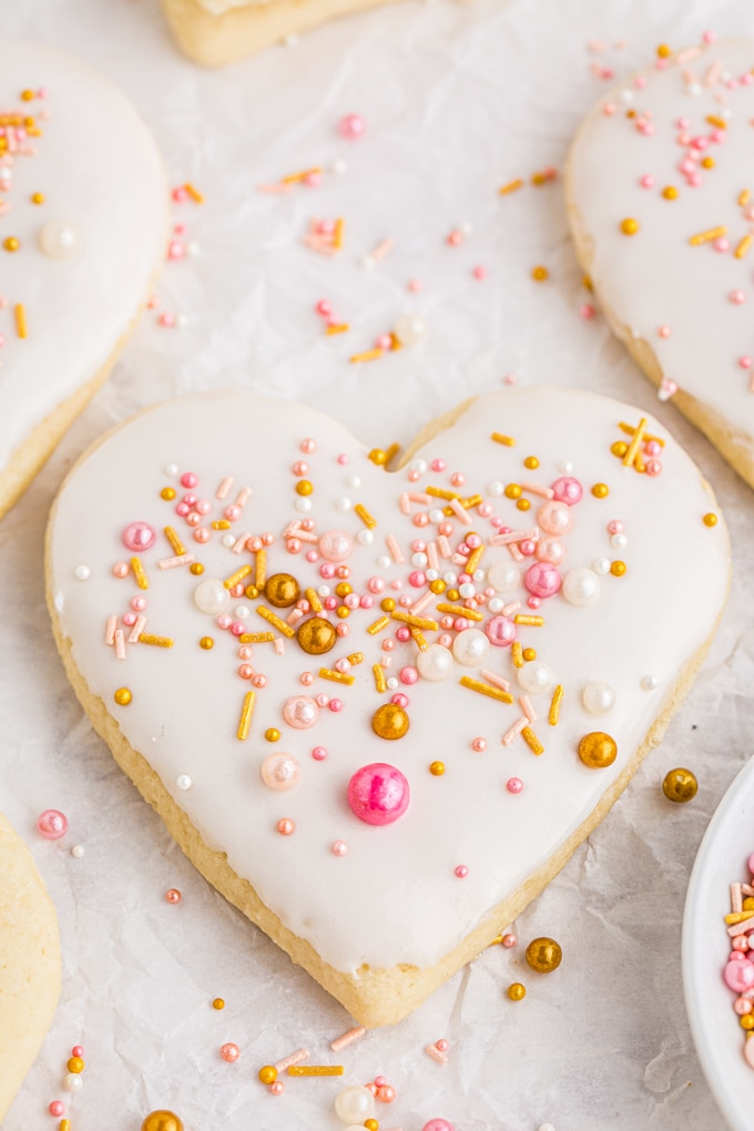 close up of heart shaped sugar cookie with white frosting and pink and gold sprinkles