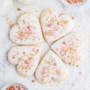 overhead photo of heart shaped Valentine's sugar cookies arranged in a circle with white frosting and pink and gold sprinkles