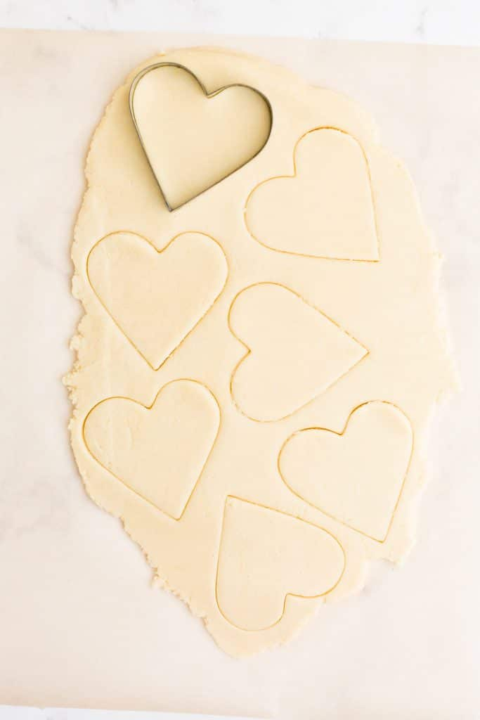 cookie dough rolled out on parchment paper with heart shapes cut into it