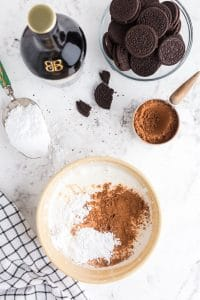 whipped cream in bowl with powdered sugar and cocoa powder sprinkled on top