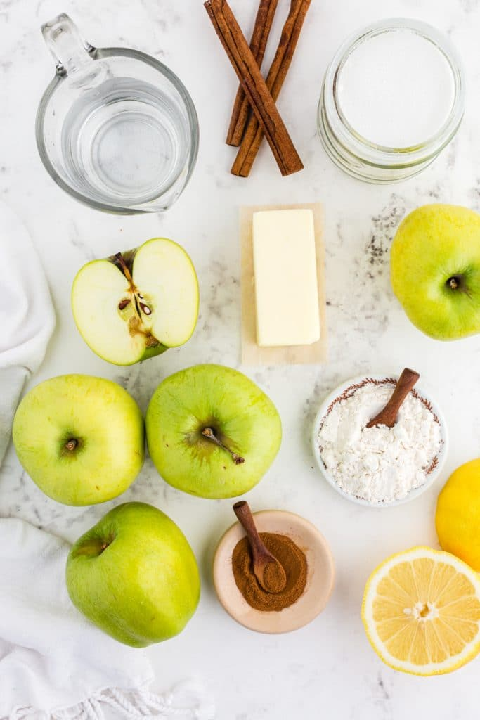 Several apples, a bowl with ground cinnamon, a bowl with flour, a lemon cut in half, butter, cinnamon sticks, glass pitcher with water on marble countertop