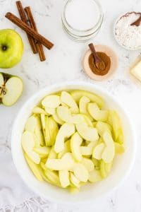 White bowl filled with apples slices, a bowl with ground cinnamon, a bowl with flour, a lemon cut in half, butter, cinnamon sticks, on marble countertop